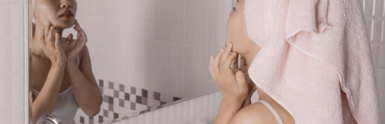 mulher adulta com acne se olhando no espelho