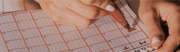 moça preenchendo calendário de mesntruação e fertilidade