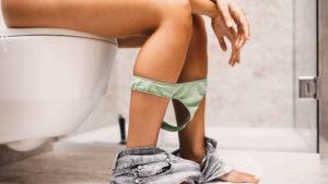 mulher no banheiro olhando corrimento